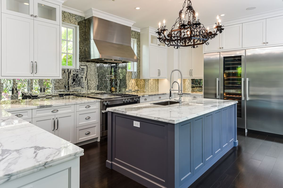 A kitchen has white cabinets, marble countertops, and a dark blue island.