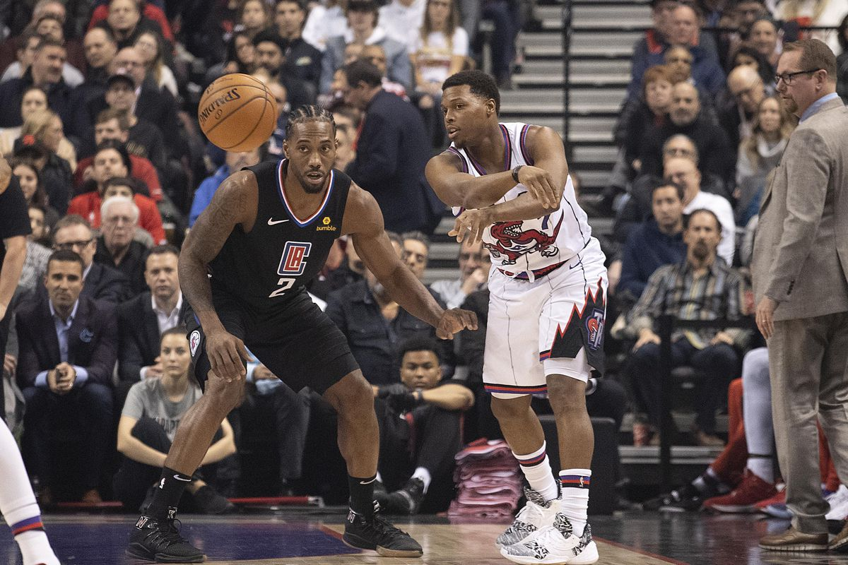 Toronto Raptors guard Kyle Lowry controls a ball as LA Clippers forward Kawhi Leonard defends during the first quarter at Scotiabank Arena.