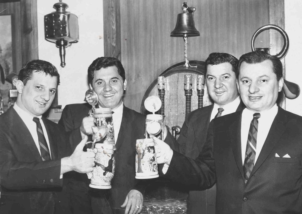 A vintage black and white photograph of four men in suits holding drinks.