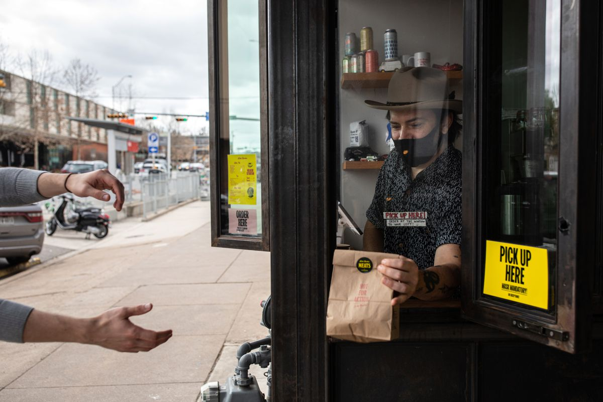 A person in a black mask and a dark gray hat is holding a brown bag through a pickup window