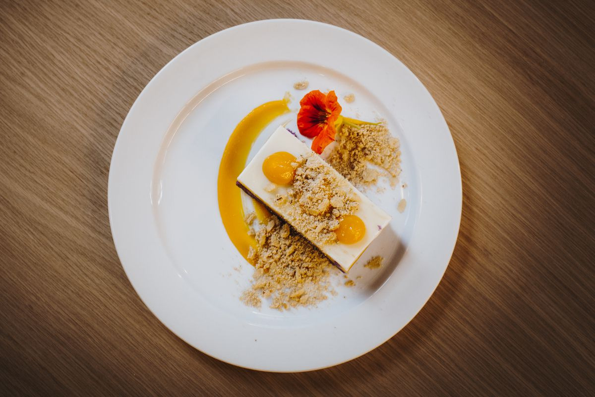 A rectangular cake slice with white frosting and yellow dots of fruit compote covered in crumble with an orange-colored flower on the plate.