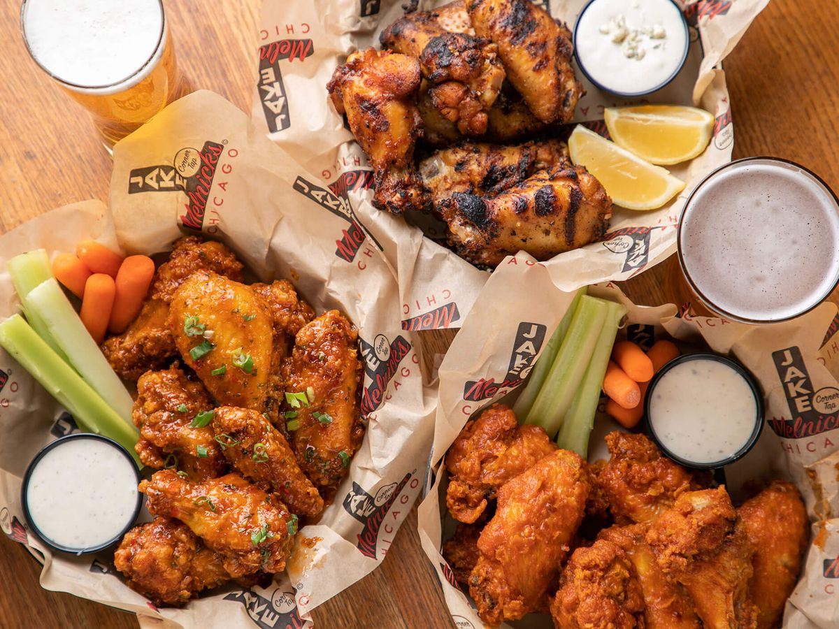 Three baskets of wings, sauces, and veggies plus pints of beer on a table.