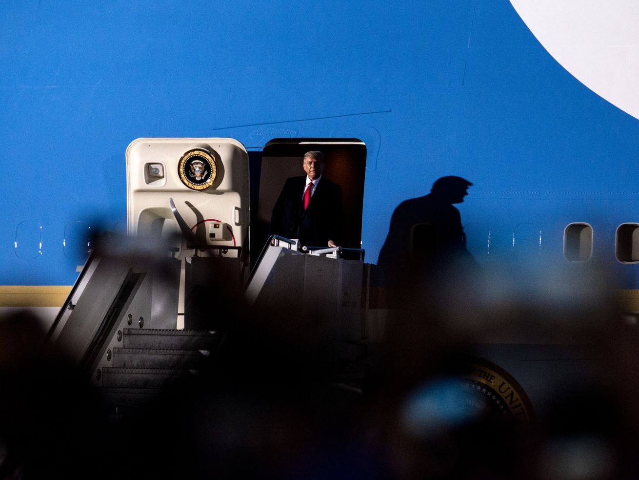President Trump standing in the doorway of the Air Force One airplane.