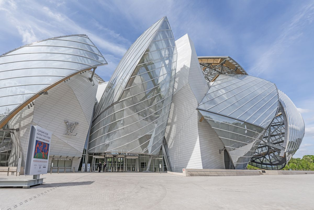 The exterior of the Louis Vuitton Foundation building in Paris. The geometric facade is glass, concrete, and wood.