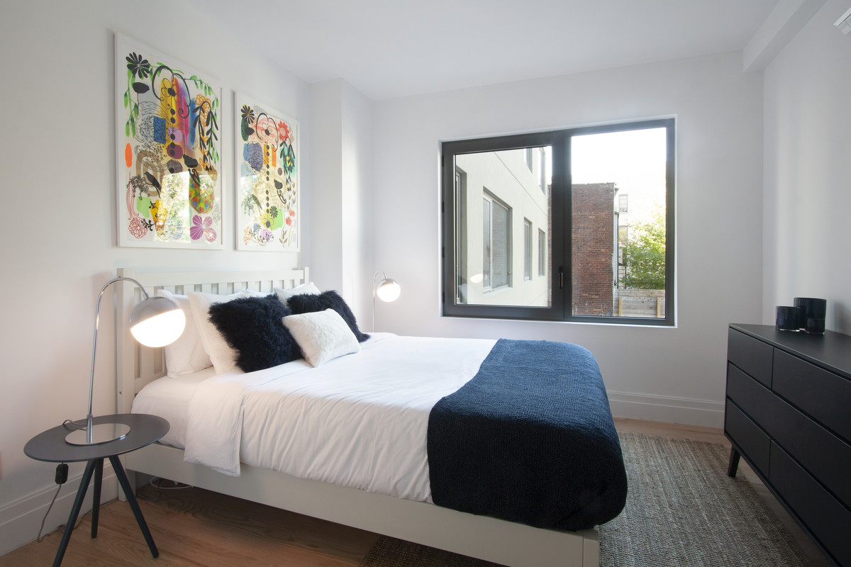 A bedroom with a medium-sized bed, a large window, and hardwood floors.