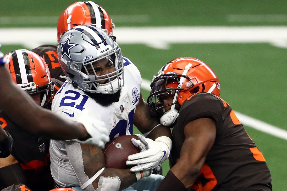 Ezekiel Elliott of the Dallas Cowboys is tackled by the Cleveland Browns defense in the fourth quarter at AT&T Stadium on October 04, 2020 in Arlington, Texas.