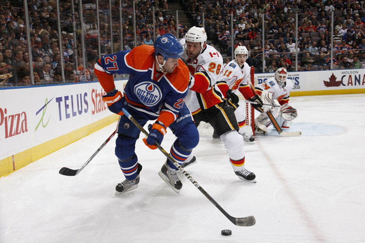 EDMONTON CANADA - OCTOBER 7:  Robyn Regehr #28 of the Calgary Flames checks Dustin Penner #27 of the Edmonton Oilers in first-period action at Rexall Place October 7 2010 in Edmonton Alberta Canada. (Photo by Dale MacMillan/Getty Images)