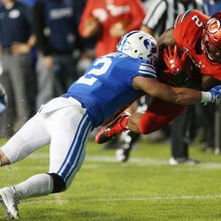 Utah Utes running back Zack Moss (2) dives for more yards against Brigham Young Cougars linebacker Matt Hadley (2) in Provo on Saturday, Sept. 9, 2017.