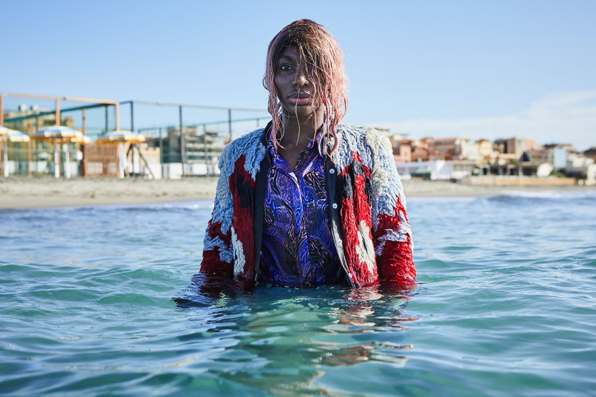 A person wearing a colorful shirt and jacket studs up to their waist in the ocean. Behind them are low-rise buildings along the shore.