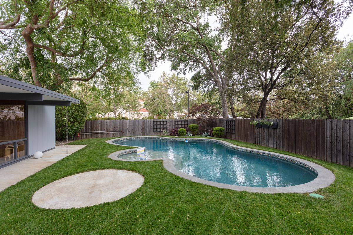 A green lawn with a pool that looks like three bubble stuck to each other.
