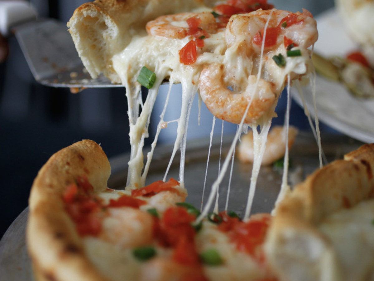 Pizza topped with shrimp, Alfredo sauce, tomato relish, green onion