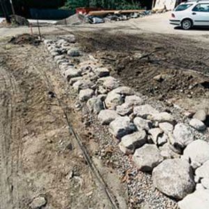 The base stones are supported by a 6- to 12-inch bed of 1/4-inch cut stone over sandy soil to prevent heaving in winter.