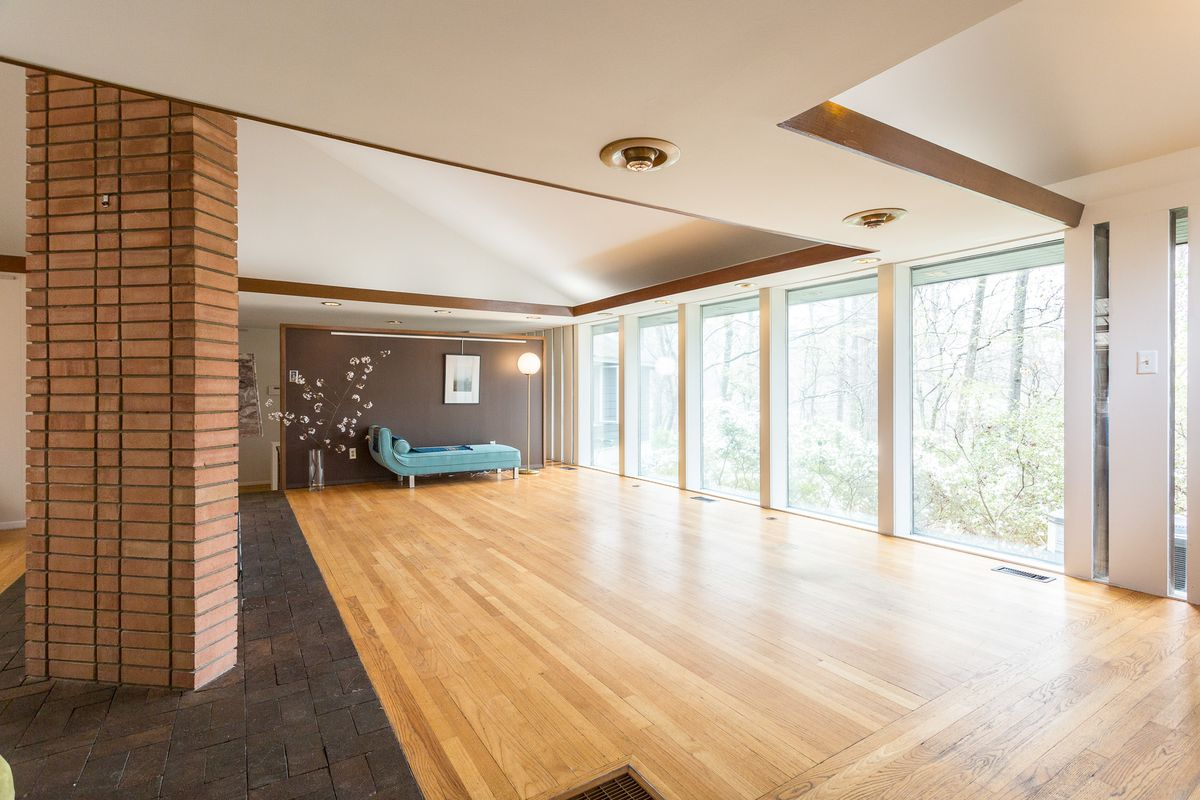 A living room has large windows on one wall, wood floors, and a day lounger on one wall.