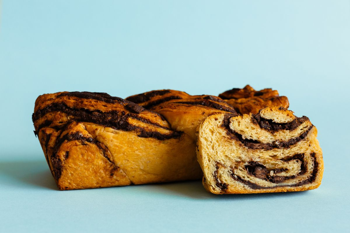 A loaf of babka with a slice shown perpendicular to show the swirls