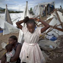 A girl ties her hair next to her tent after it fell down due to heavy rain at a camp for earthquake survivors in Port-au-Prince, Haiti, Saturday, Sept. 25, 2010.