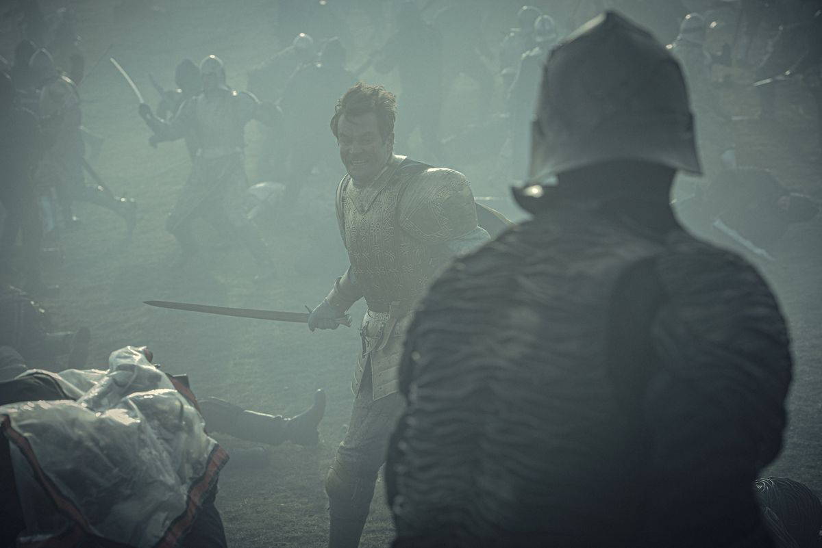 a man in armor swings a sword as his opponent