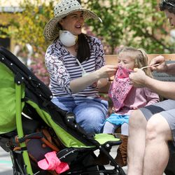 Denise Haynie covers 2-year-old Nora Haynie's cough with a bandana she uses as a mask while her husband Dave Haynie continues to feed her ice cream at the Hogle Zoo in Salt Lake City on Saturday, May 2, 2020. The zoo reopened to guests after closing because of the COVID-19 pandemic in March. It has new regulations in place to help avoid the spread of the virus.