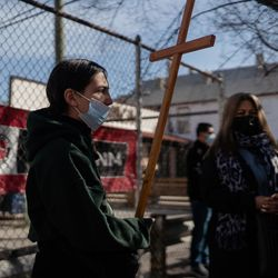 A person joins the Via Crucis procession in Pilsen, Friday morning, April 2, 2021. The annual Via Crucis is a Good Friday tradition that reenacts the Stations of the Cross, a Catholic devotion that recounts Jesus' passion and death.