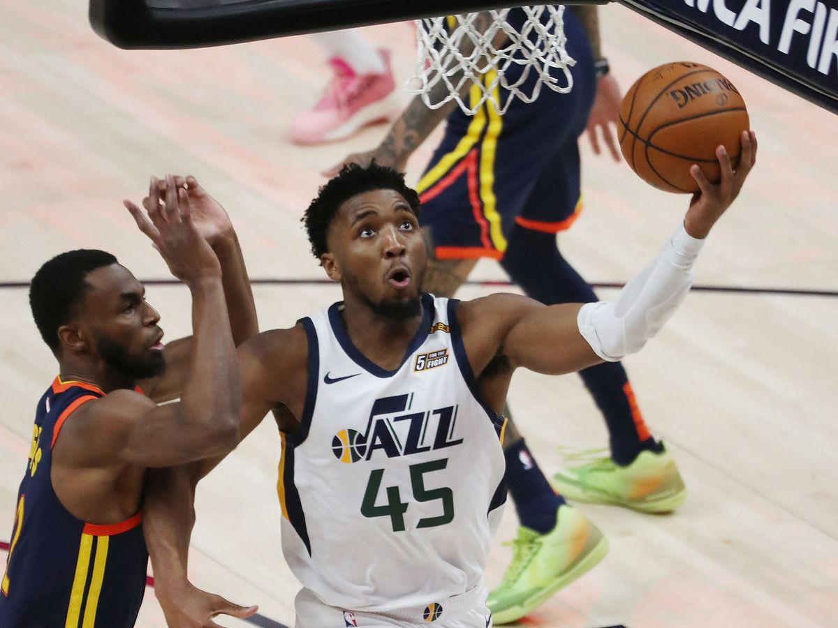 Utah Jazz guard Donovan Mitchell (45) drives against Golden State Warriors forward Andrew Wiggins (22) in Salt Lake City on Saturday, Jan. 23, 2021.