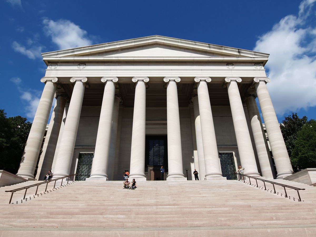 The exterior of the National Gallery of Art in Washington D.C. There is a large staircase and columns on the front of the facade.