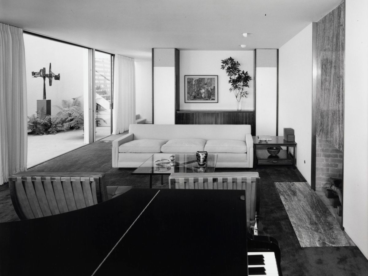 A white living room furnished with a rectangular sofa and a grand piano. A glass sliding door leads outside.