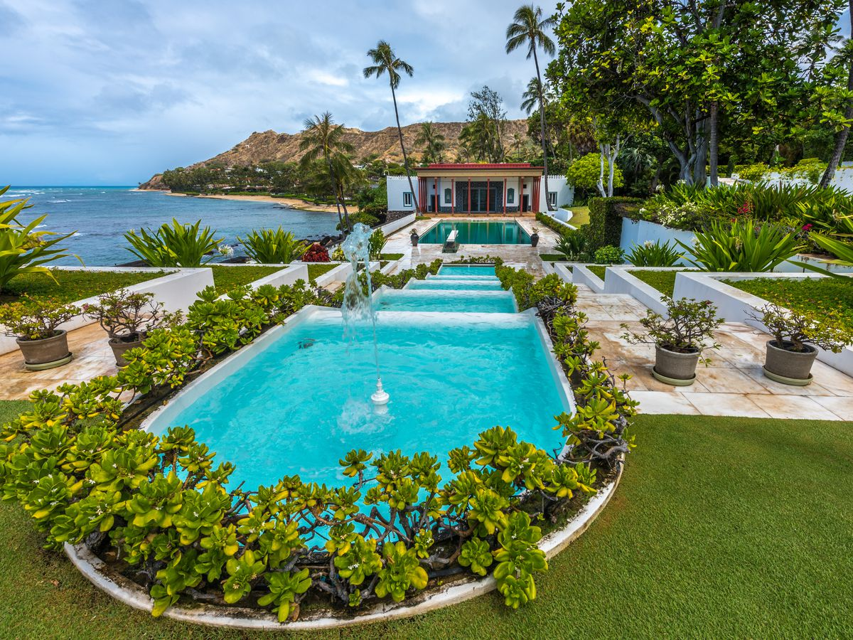 A low-slung house with a huge round pool in front, and ocean to the back.