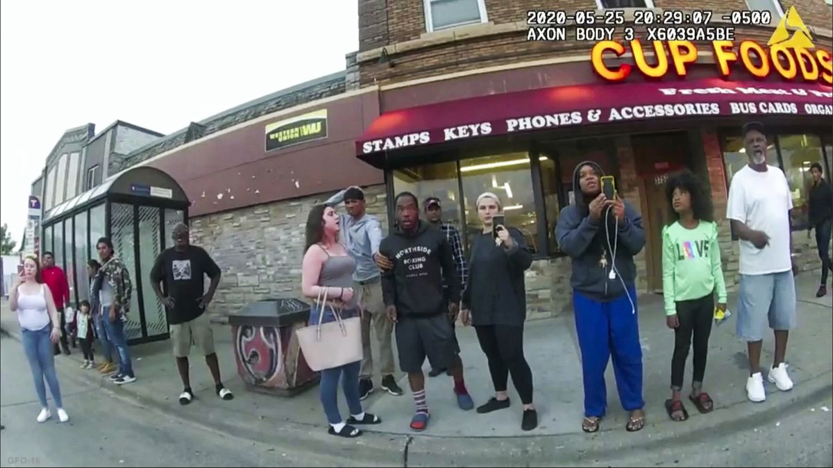 A fisheye view of the scene outside Cup Foods as Floyd died; Frazier and other bystanders film; Martin looks on. Some bystanders are in a bus shelter waiting for the bus. In the top right hand corner is the date and time.