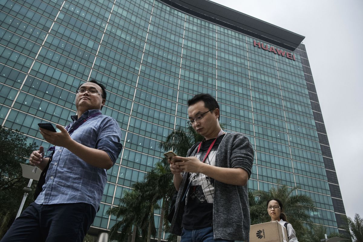 Two men look at their phones outside the Huawei building in China.