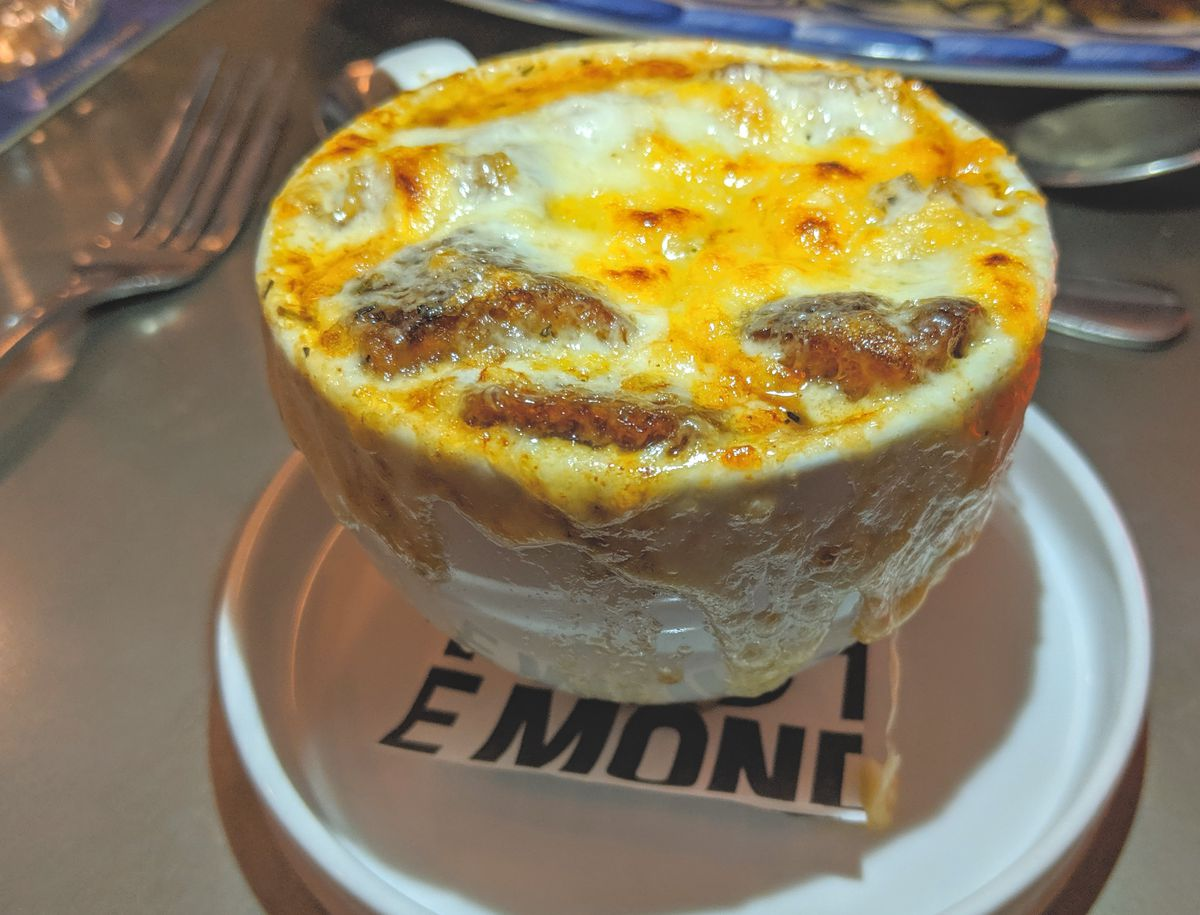French onion soup sits in a white bowl on a white saucer. The cheese on top is browned in spots and is melted over the edges of the bowl.