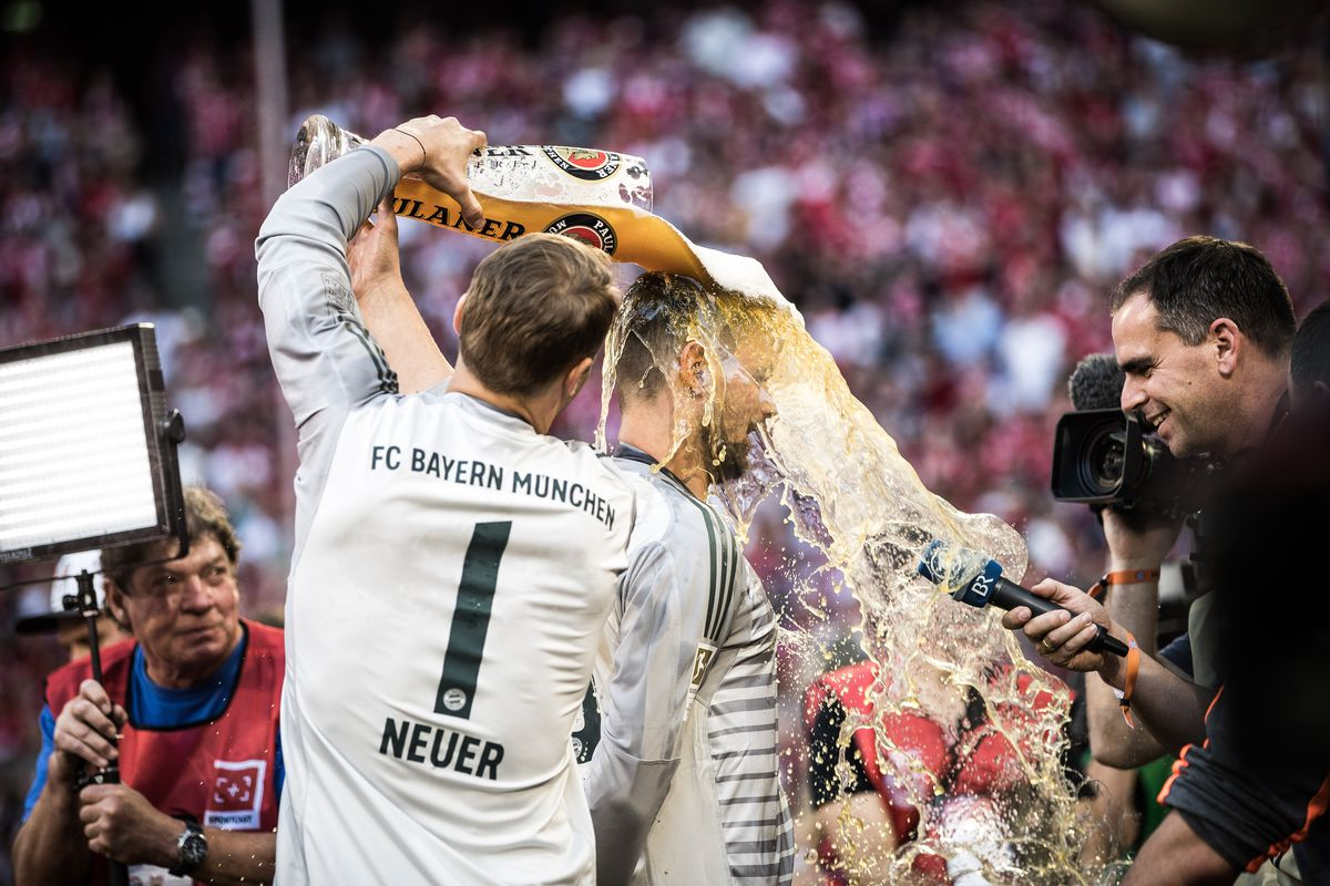 FC Bayern Muenchen v VfB Stuttgart - Bundesliga MUNICH, GERMANY - MAY 12: Sven Ulreich of Bayern Munich gets beer shower by Manuel Neuer of Bayern Munich during the celebration for the 28th German football championship after the Bundesliga match between FC Bayern Muenchen and VfB Stuttgart at Allianz Arena on May 12, 2018 in Munich, Germany.