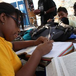"""In this Tuesday, Oct. 11, 2010 photo, Trinity Taylor, 10, works on her homework outside the Blackstone Bicycle Works bike shop in Chicago as Tyjuan Edwards, the shop's youth mentor, stands in the background. The facility has an after-school program and gives students the chance to work 25 hours in the shop to earn a bike. At Blackstone, there are clear expectations. If you don""""™t go to school, for instance, you can""""™t come to the program. Respect is a must, as is cleaning up after yourself. You have to finish your homework before fixing or riding bikes or throwing a football."""
