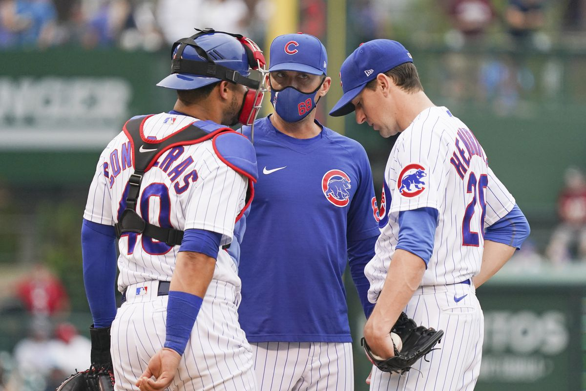 Cubs pitching coach Tommy Hottovy talks with Kyle Hendricks and Willson Contreras.