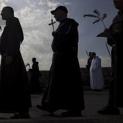 Christian clergymen participate in the traditional Palm Sunday procession on the Mount of Olives, overlooking Jerusalem's Old City, Sunday, April 1, 2012. Palm Sunday marks for Christians, Jesus Christ's entrance into Jerusalem, when his followers laid palm branches in his path, prior to his crucifixion.