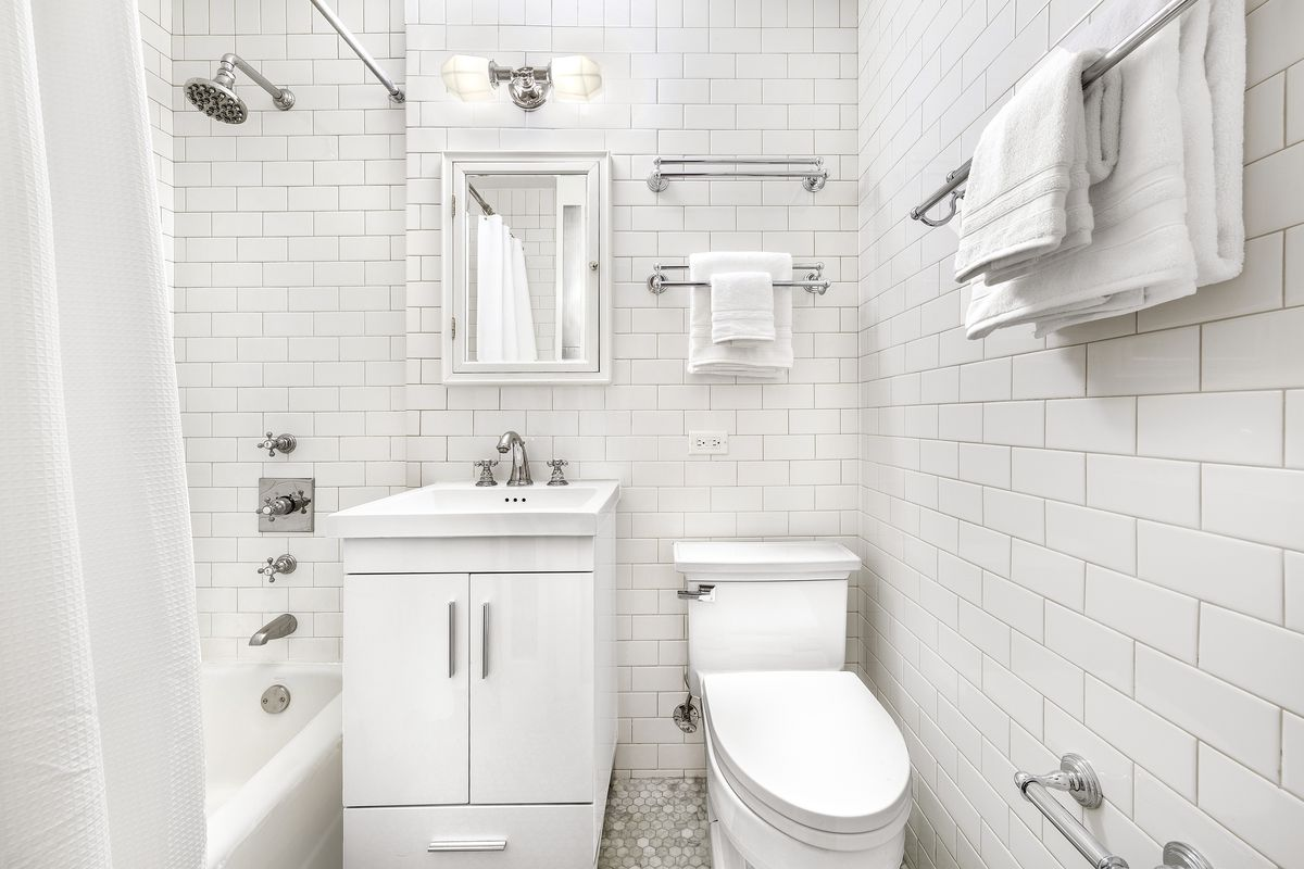 A bathroom with marble floors, white tiles, and chrome fixtures.
