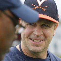 Virginia football coach Bronco Mendenhall talks to a fellow coach after spring football practice at their indoor facility in Charlottesville, Va., on April 6, 2017.