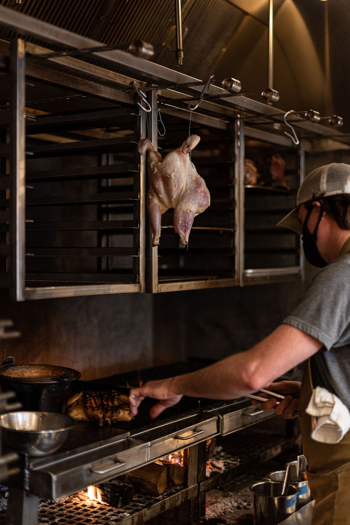 A worker touches meat on a live fire grill as chicken hangs above.