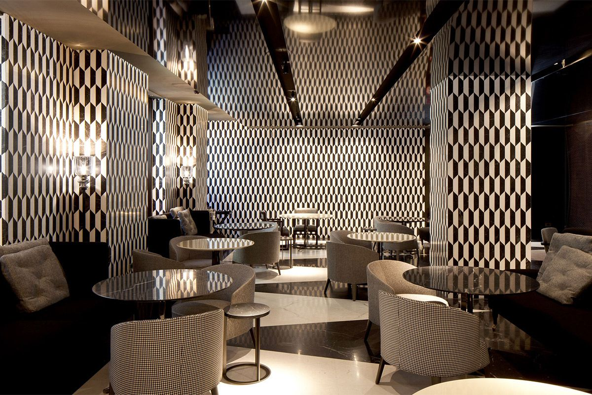 The interior of the Mandarin Oriental in Milan. The walls are decorated in a black and white mosaic pattern. There are chairs and tables.