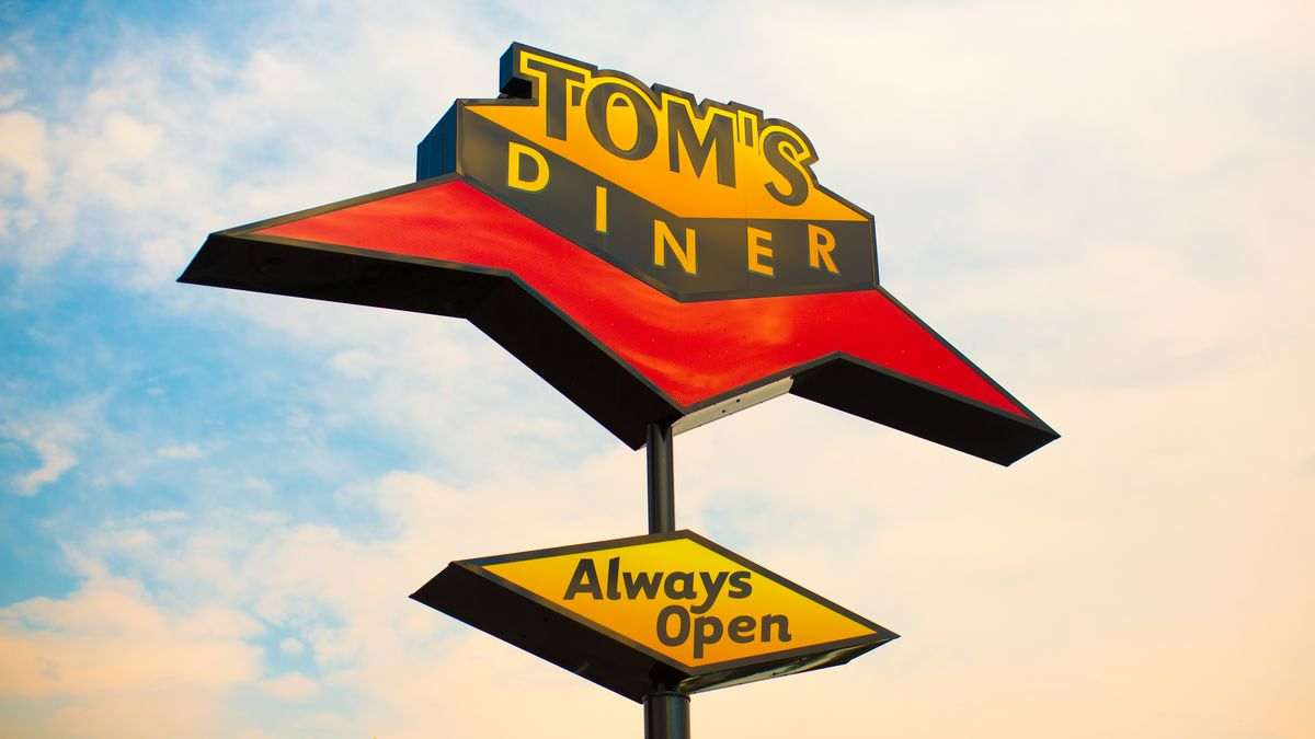 "Against a blue sky, a Googie-style sign that says: ""Tom's Diner. Always Open."""