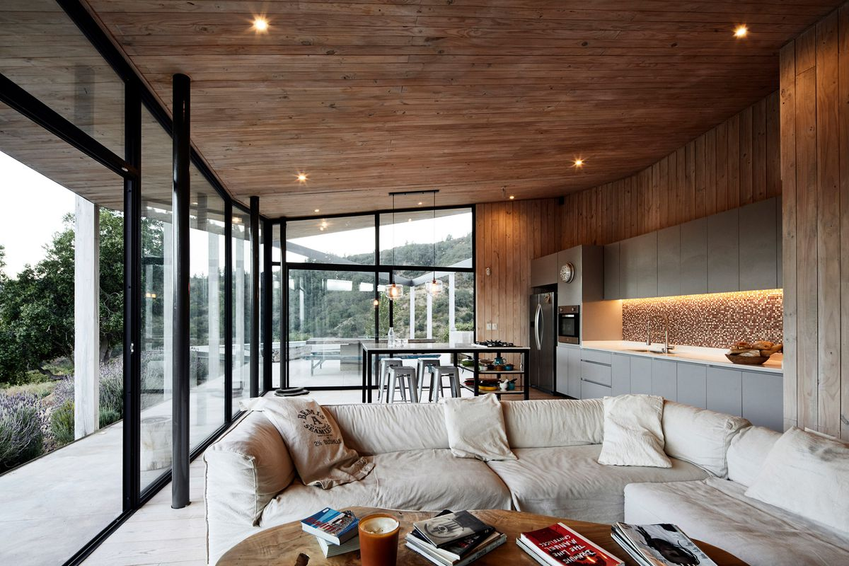 Open living area connecting to a kitchen and dining area. There's a large off-white couch, timber ceilings and walls, and expansive glass walls opening up to a wraparound terrace.