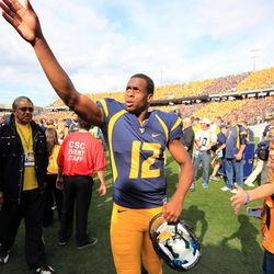 West Virginia quarterback Geno Smith gestures to fans after their NCAA college football game against Baylor in Morgantown, W.Va., Saturday, Sept. 29, 2012. Smith threw for 656 yards and tied a Big 12 record with eight touchdown passes to lead No. 9 West Virginia to a 70-63 win over No. 25 Baylor .