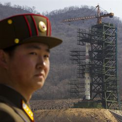 A North Korean soldier stands in front of the country's Unha-3 rocket, slated for liftoff between April 12-16.