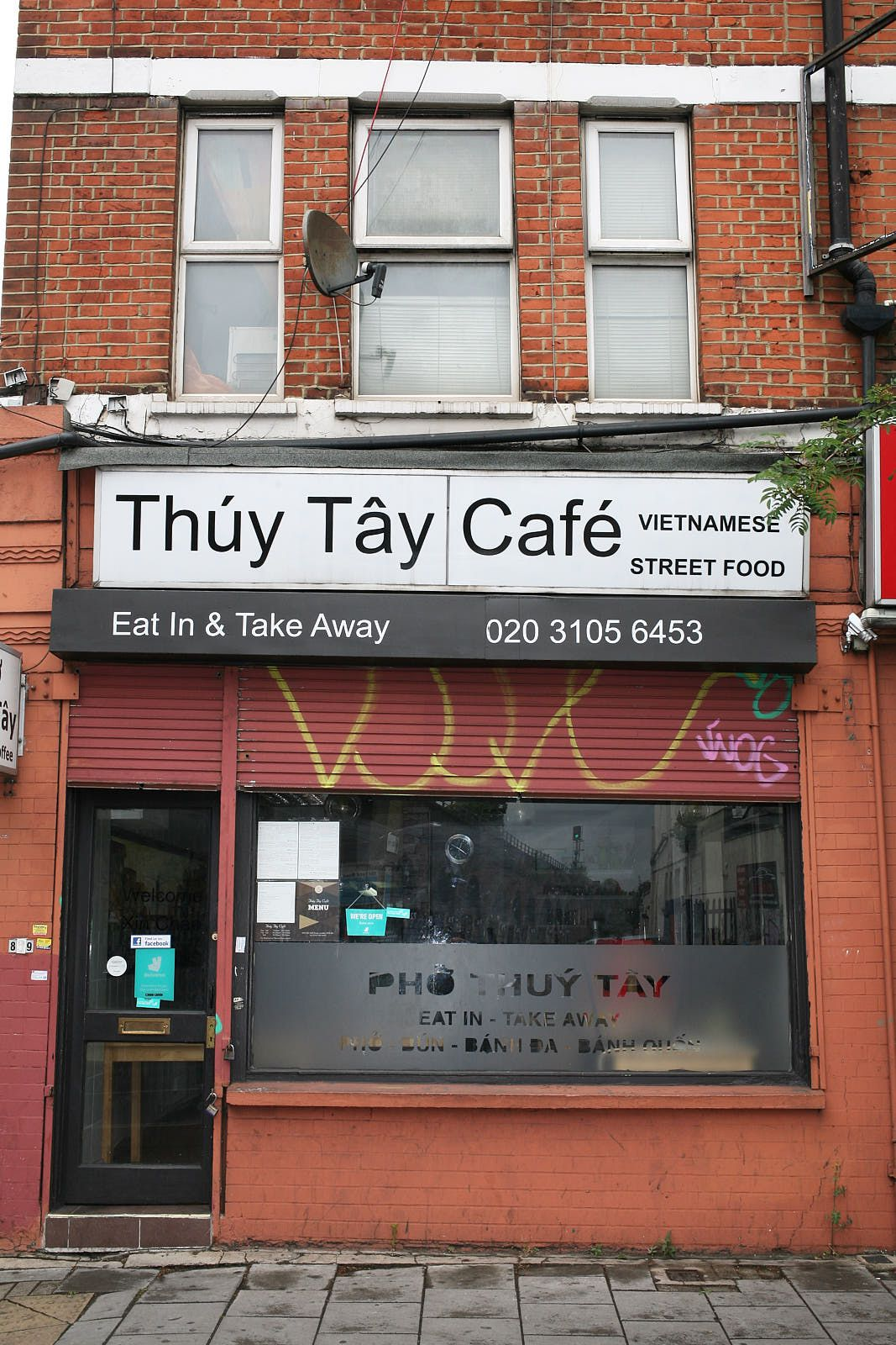 The exterior of Pho Thuy Tay Vietnamese restaurant on Old Kent Road, London, with bricks surrounding a white sign with Pho Thuy Tay written in black text