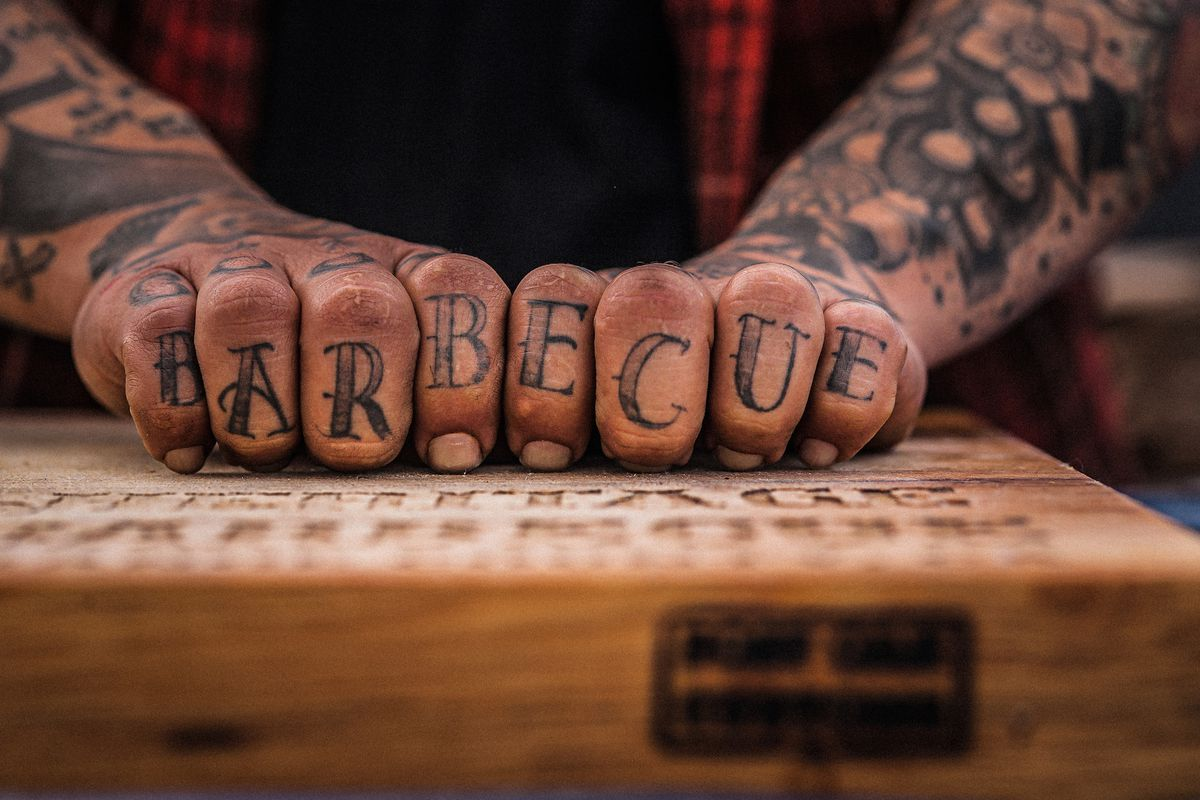 Knuckle tattoos that spell out Barbecue.