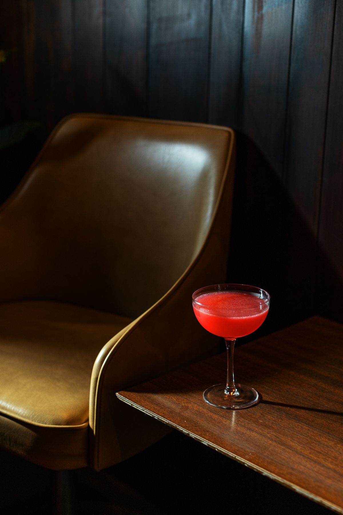 A raspberry red cocktail served in a coup sits on a wooden table next to a mid-century chair.