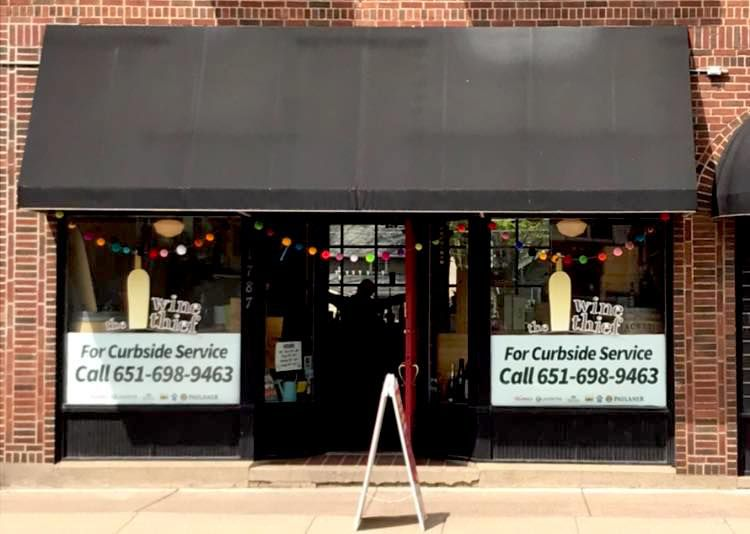 The charming facade has a black awning, brick building and large windows.