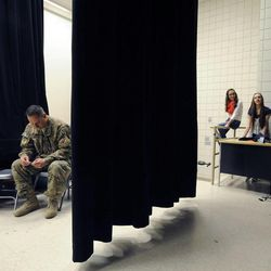 Air Force Tech Sgt. Edward Goettig takes a moment on the stage while waiting to surprise his two daughters Addie and Olivia at Fox Hollow Elementary School on Thursday, March 6, 2014. Goettig had been deployed to Afghanistan since Aug. 27, 2013.