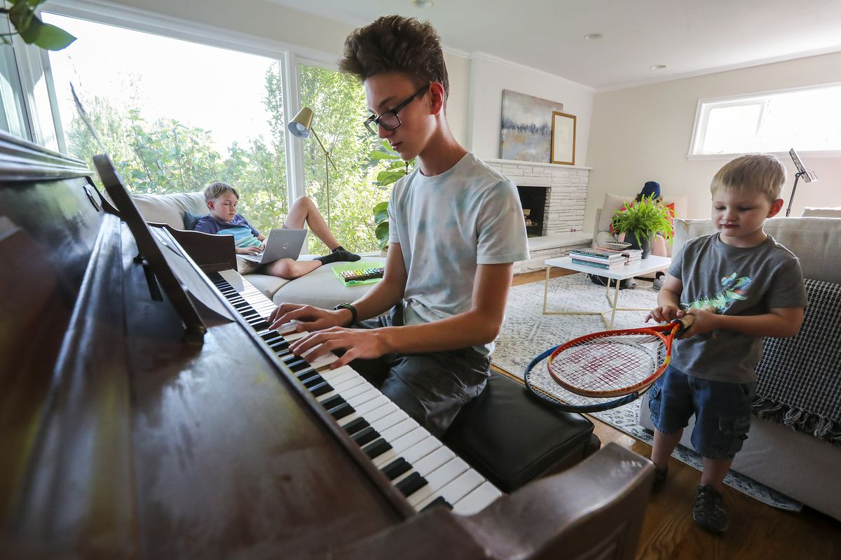 Peter Larsen practices the piano as his brother Eric works on a computer and little brother George plays with a pair of tennis racquets at their home in Salt Lake City on Wednesday, Sept. 16, 2020.