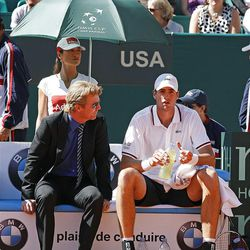 U.S. team captain Jim Courier,left, speaks to U.S. player John Isner during his match against French tennis player Jo-Wilfried Tsonga, in the quarterfinal of the Davis Cup between France and U.S. in Monaco Sunday April 8, 2012. John Isner won the match and qualifies the U.S. team for the semi-final.(AP Photo/Remy de la Mauviniere)
