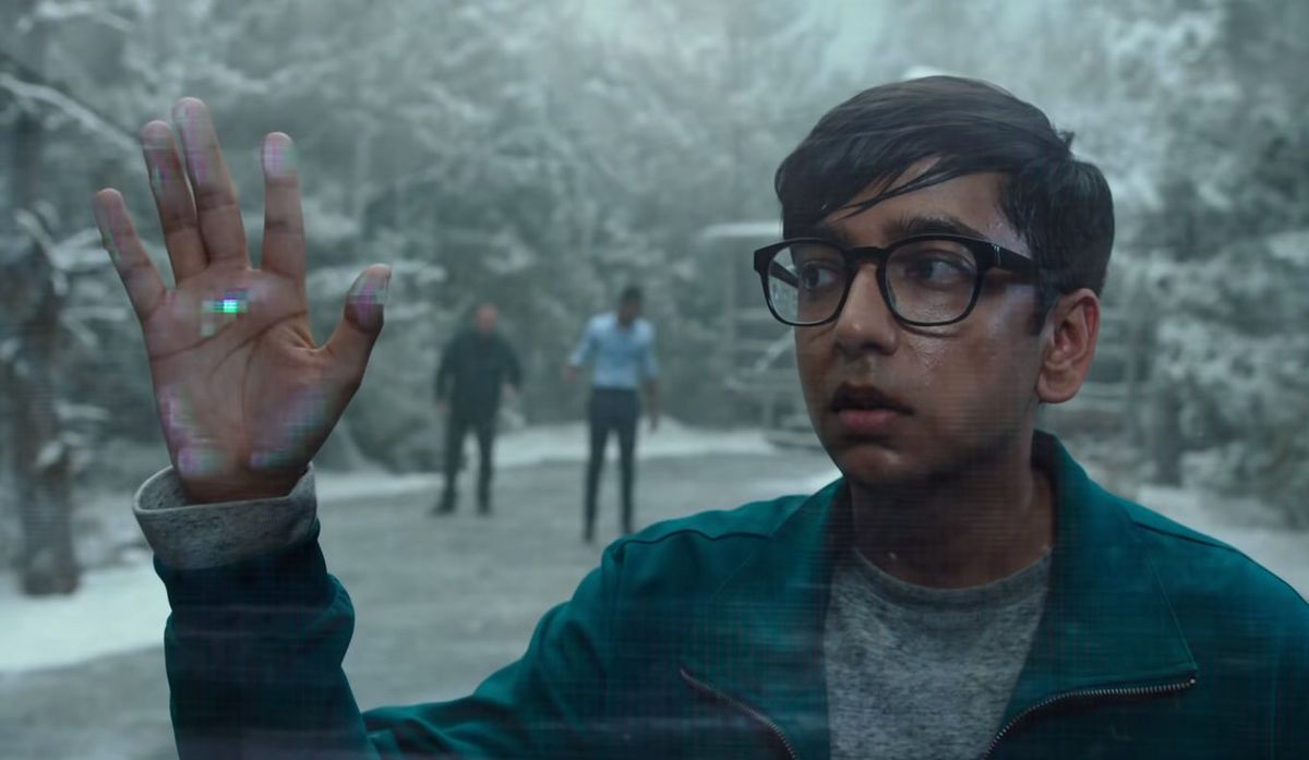 A young man with glasses standing on what appears to be a snowy road outside puts his hand up to the fourth wall and encounters a glitchy force field in 2019's Escape Room