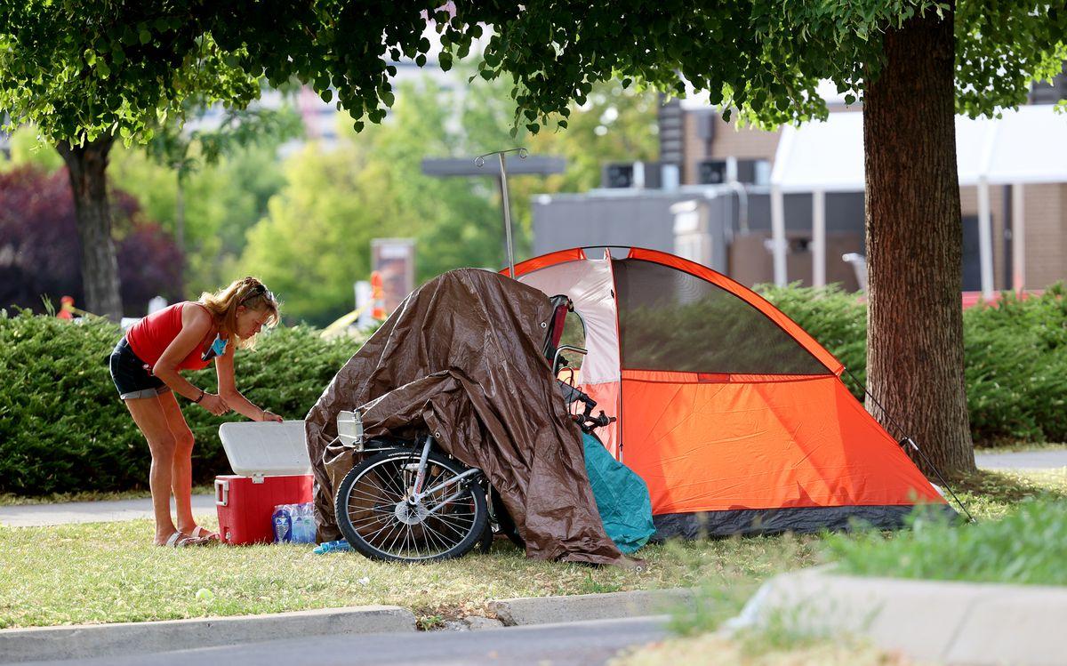 A woman opens a cooler as she walks around a homeless campsite.